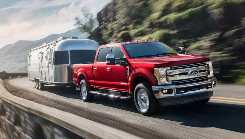 2019 Ford Super Duty Lariat red pulling camper trailer on side of mountain
