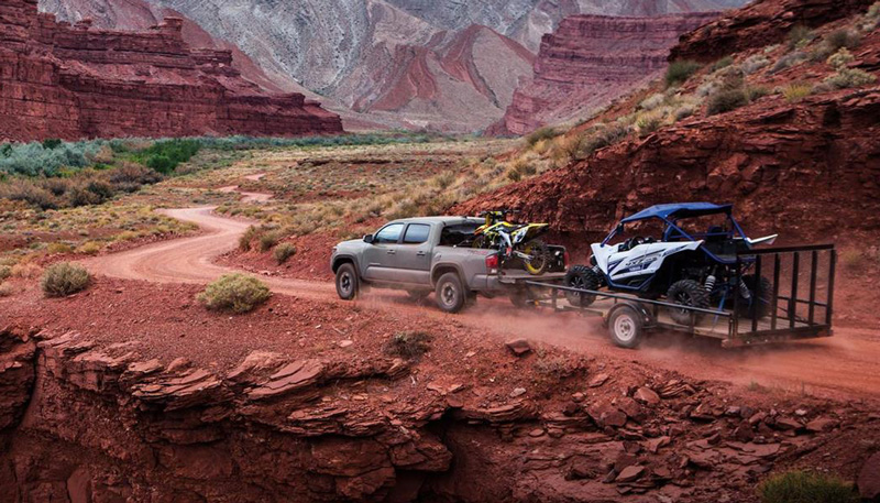 gray 2018 toyota tacoma pulling trailer with dune buggy in a mountain canyon