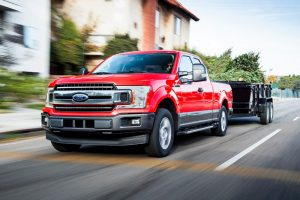 red 2018 ford f 150 pulling black trailer down the road.jpg